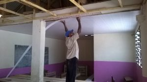 Carpenter fixing new ceiling in dining hall